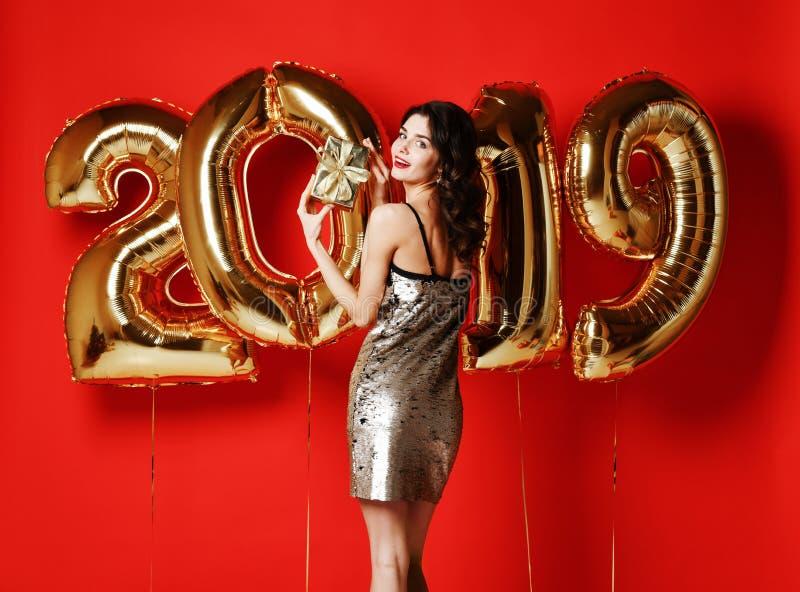Portrait d'une jeune fille étonnée de sourire dans le boîte-cadeau brillant d'or d'apparence de robe et de regarder la caméra images libres de droits