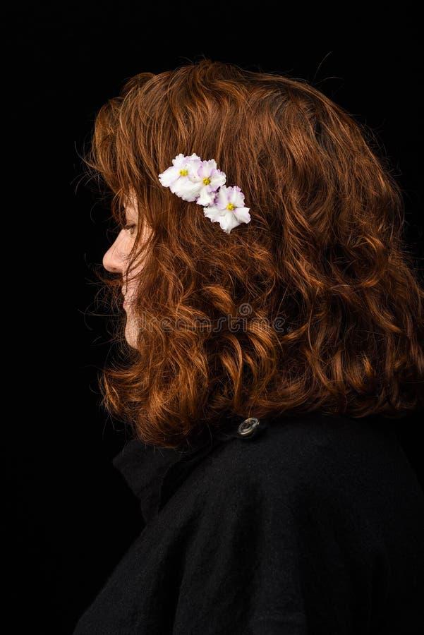Portrait d'une jeune fille avec des violettes de Saintpaulia dans ses cheveux glamor Tendances de beauté Protection de cheveux de photo libre de droits