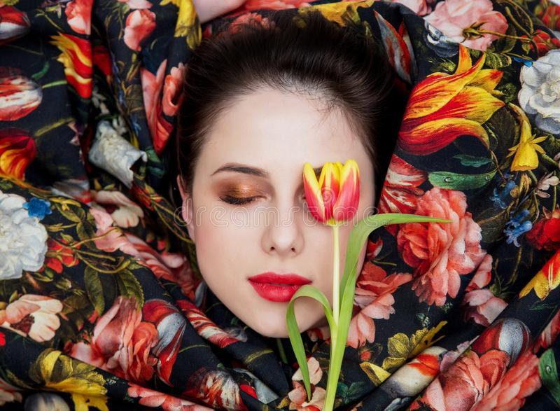 Portrait d'une jeune fille avec le rouge à lèvres rouge et le tissu enveloppé de fleur photos libres de droits
