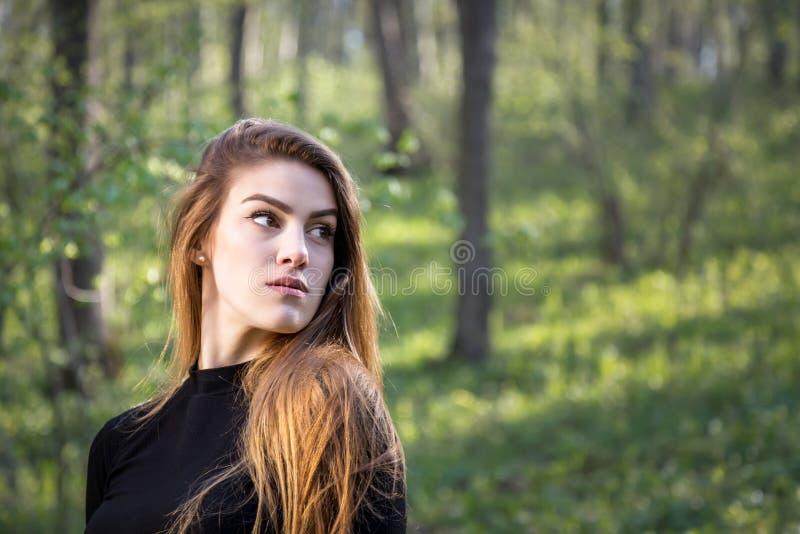 Portrait d'une jeune fille blonde dans la forêt regardant loin image libre de droits