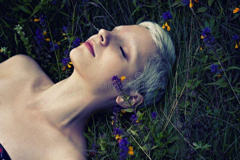Portrait d'une jeune fille blonde se trouvant sur une herbe de forêt photos stock