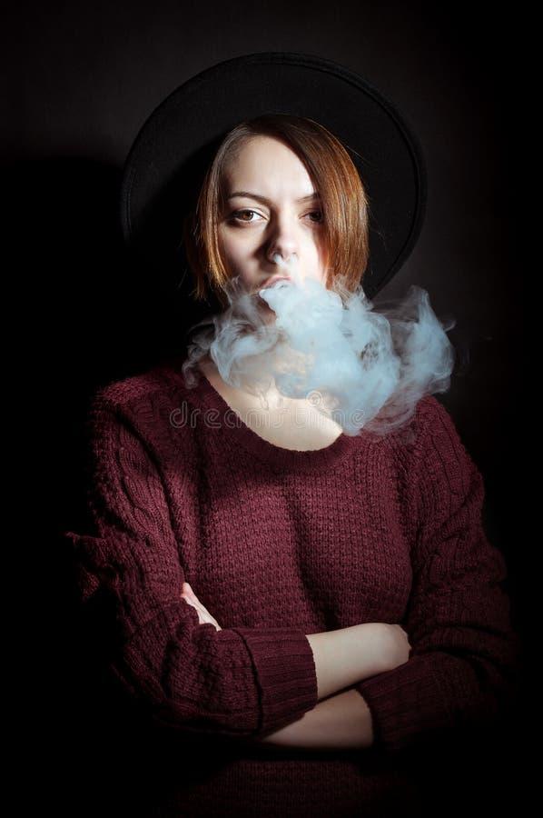 Portrait d'une jeune fille dans la fumée des cigarettes photographie stock libre de droits
