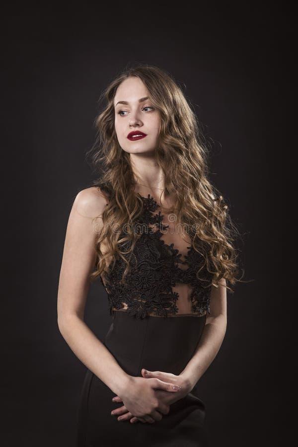 Portrait d'une jeune fille dans la robe de dentelle sur un fond noir image libre de droits