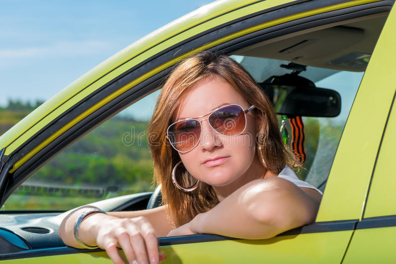 Portrait d'une jeune fille dans sa voiture photo stock