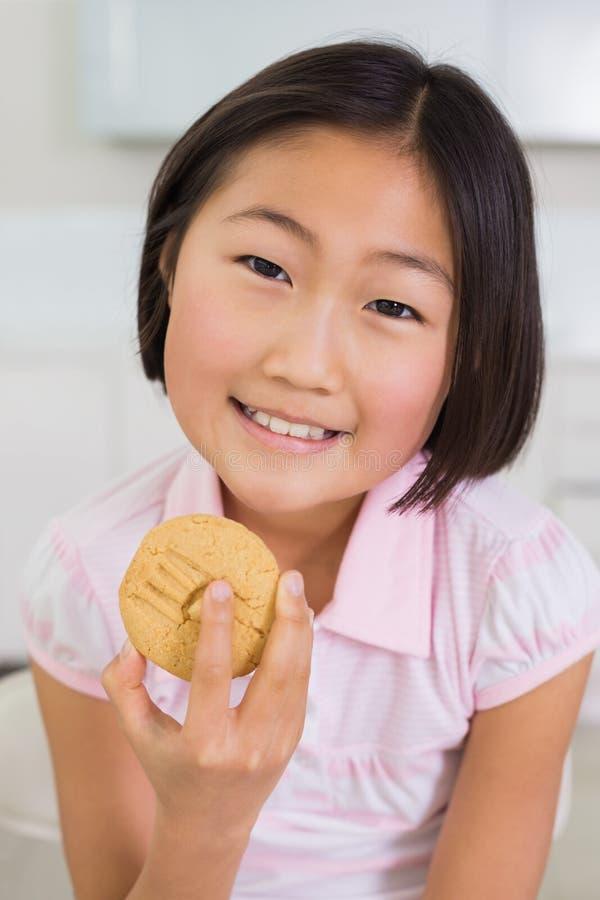 Portrait d'une jeune fille de sourire appréciant le biscuit image stock