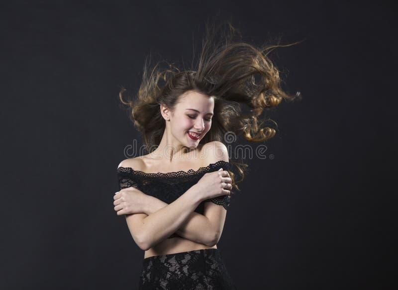 Portrait d'une jeune fille de sourire dans une robe de dentelle sur un fond noir photos libres de droits