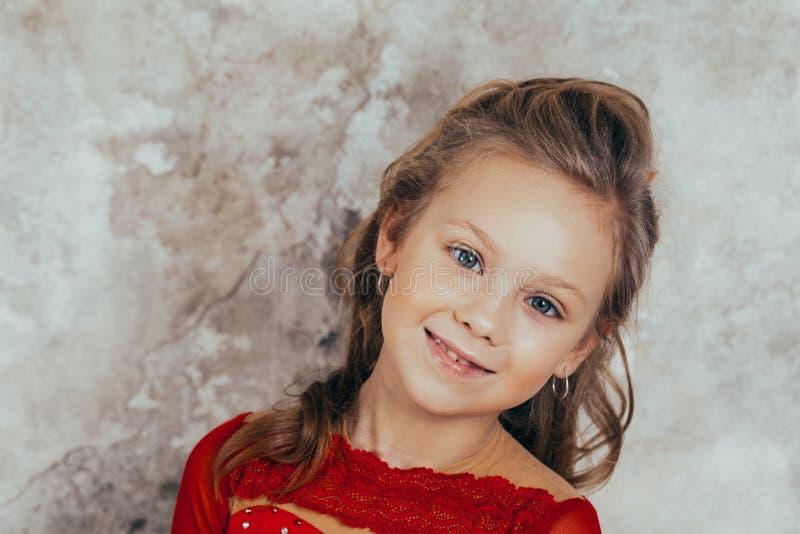 Portrait d'une jeune fille de sourire dans une robe rouge et avec une belle coiffure Projectile de studio images libres de droits