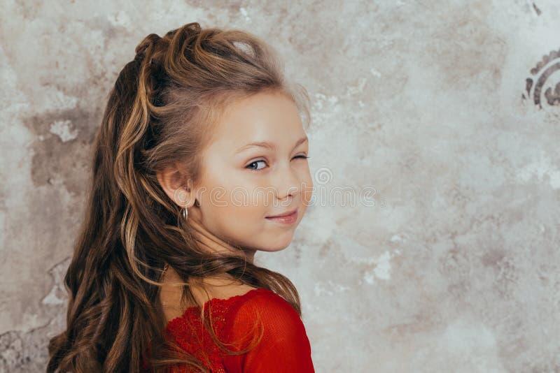 Portrait d'une jeune fille de sourire dans une robe rouge et avec une belle coiffure Projectile de studio image stock