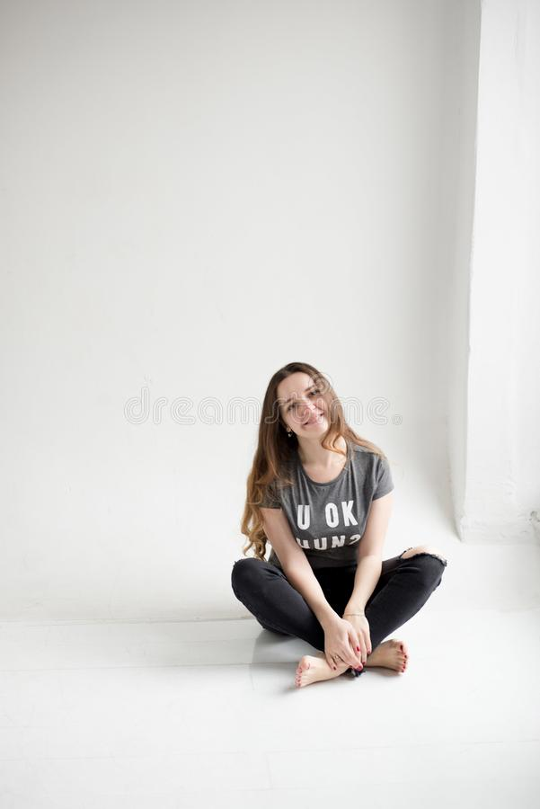 Portrait d'une jeune fille de sourire s'asseyant avec des jambes croisées d'isolement sur le fond blanc photos libres de droits