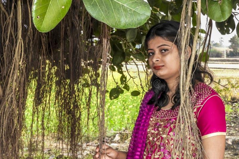 Portrait d'une jeune fille indienne se reposant sous un banian, portant la robe traditionnelle photographie stock libre de droits