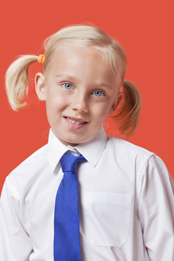 Portrait d'une jeune fille mignonne dans l'uniforme scolaire au-dessus du fond bleu photos libres de droits