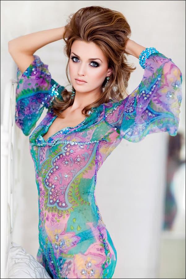 Portrait d'une jeune fille mince sensuelle avec le bleu dans une robe bleue photographie stock