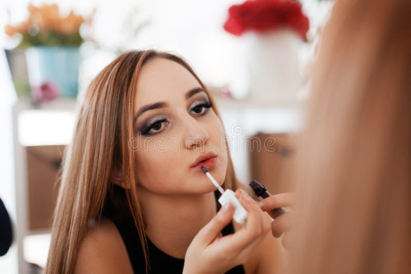 Portrait d'une jeune fille qui faisant un maquillage appliquant le rouge à lèvres photos stock