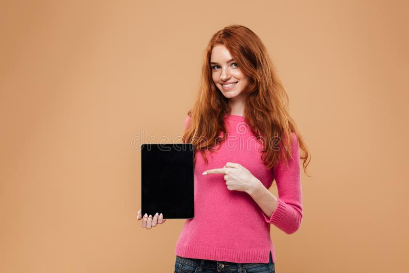 Portrait d'une jeune fille rousse de sourire dirigeant le doigt images stock