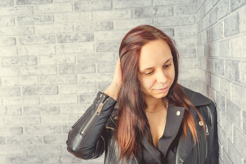 Portrait d'une jeune fille sans maquillage sur son visage dans une veste noire contre un mur de briques gris image libre de droits