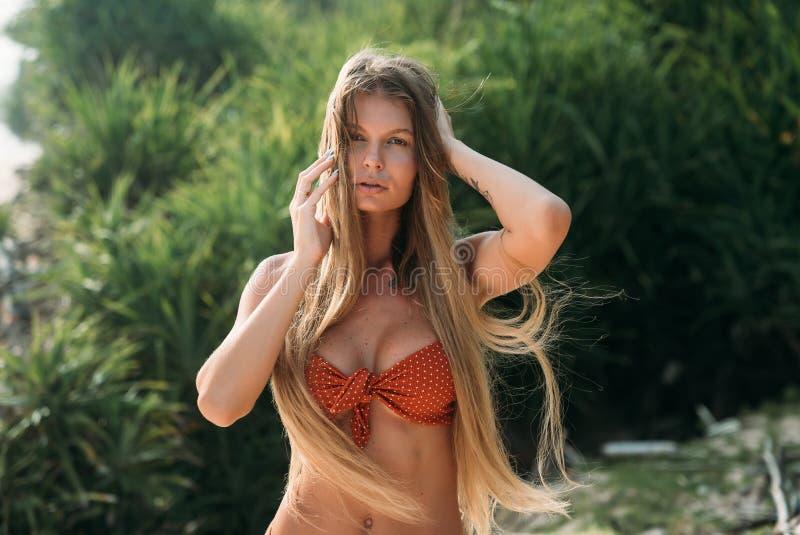 Portrait d'une jeune fille sexy avec la peau saine bronzée et les longs cheveux blonds dans un maillot de bain à la mode Les squi photo libre de droits