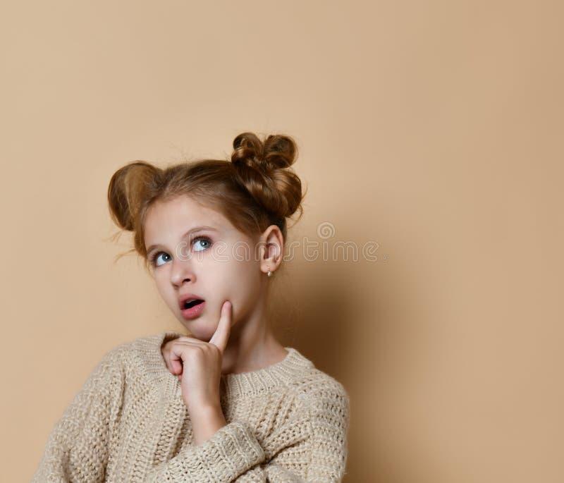 Portrait d'une jeune fille songeuse se tenant et regardant loin l'espace de copie d'isolement au-dessus du fond beige photo stock