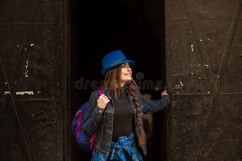 Portrait d'une jeune fille sur le fond du vieux portail noir dans la ville de Lviv image libre de droits