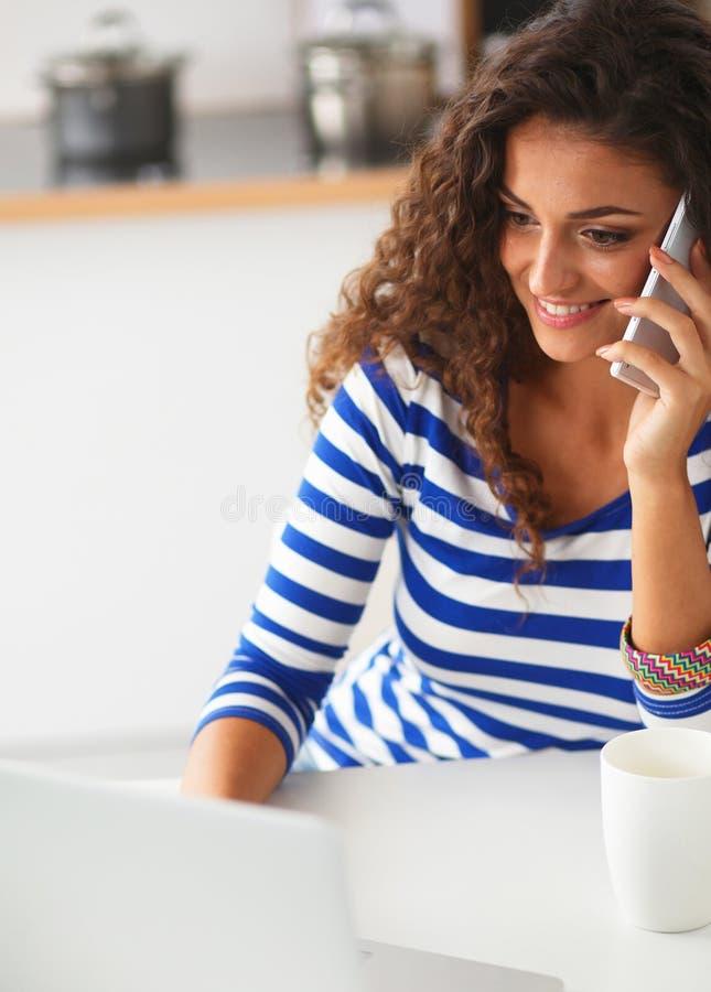 Download Portrait D'une Jeune Jolie Femme Parlant Le Téléphone Et Travaillant Sur L'ordinateur Portable Dans La Cuisine Photo stock - Image du table, fille: 87700756