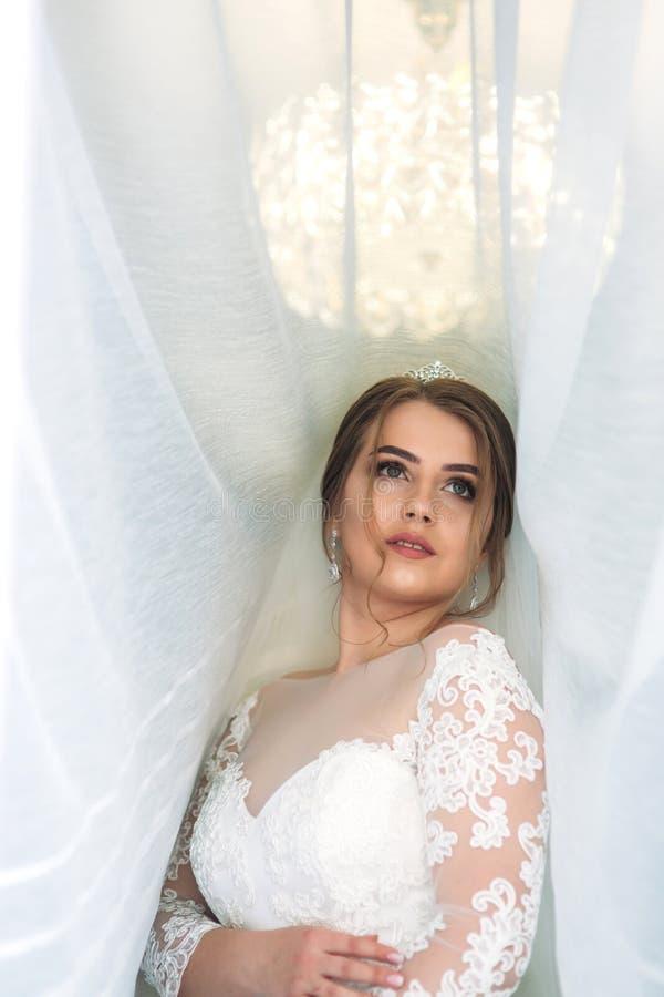 Portrait d'une jeune mariée dans une robe de mariage sous le rideau blanc photographie stock libre de droits