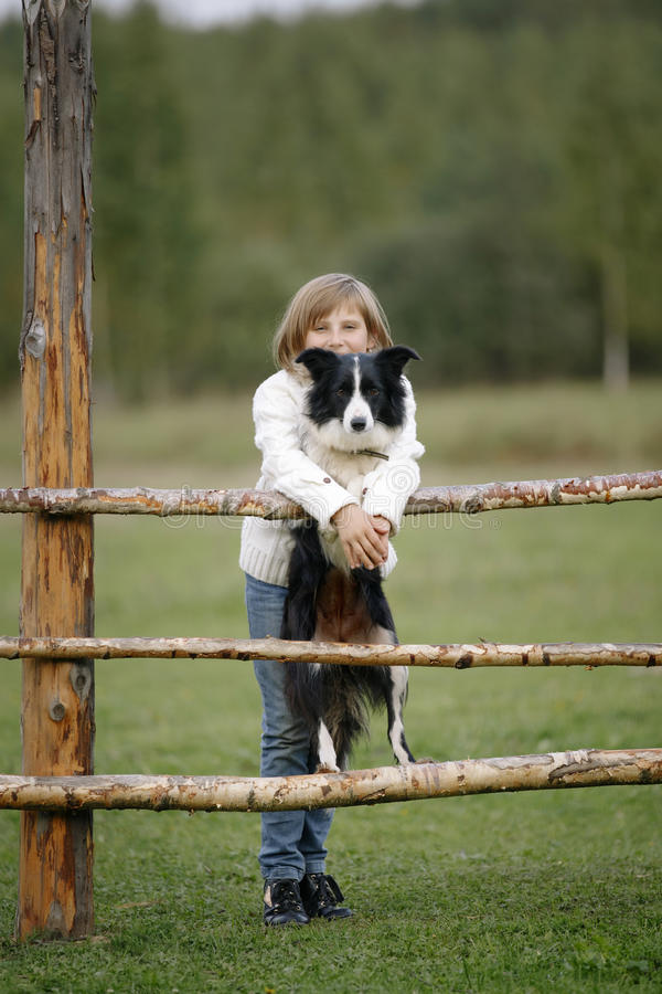 Portrait d'une jeune petite fille avec la race border collie de chien outdoors lifestyle images libres de droits