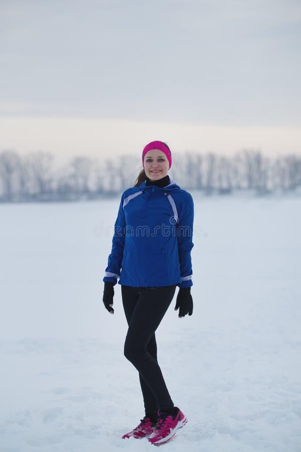 Portrait d'une jeune sportive féminine de sourire dans le domaine de glace d'hiver photographie stock libre de droits
