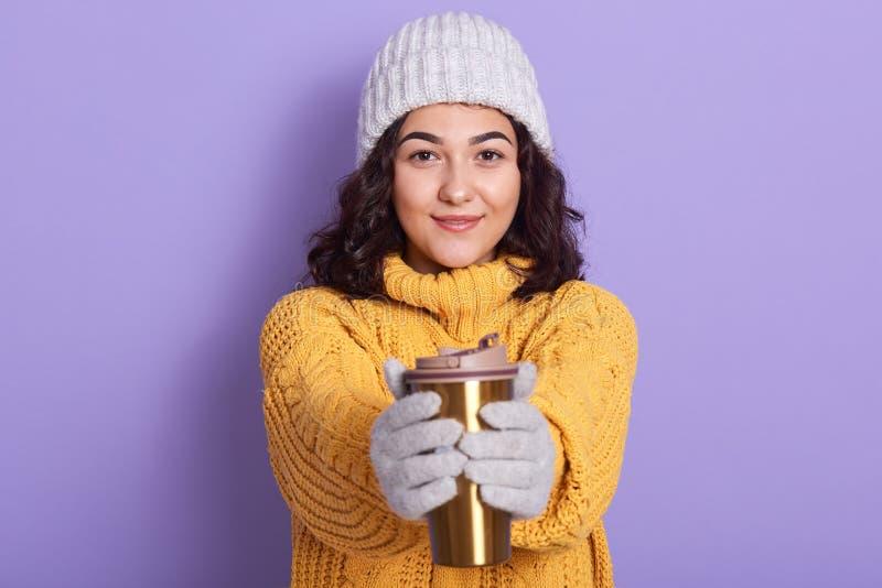 Portrait d'une jolie femme magnétique qui regarde directement la caméra, tenant le thermo dans les deux mains, se réchauffant les photos libres de droits