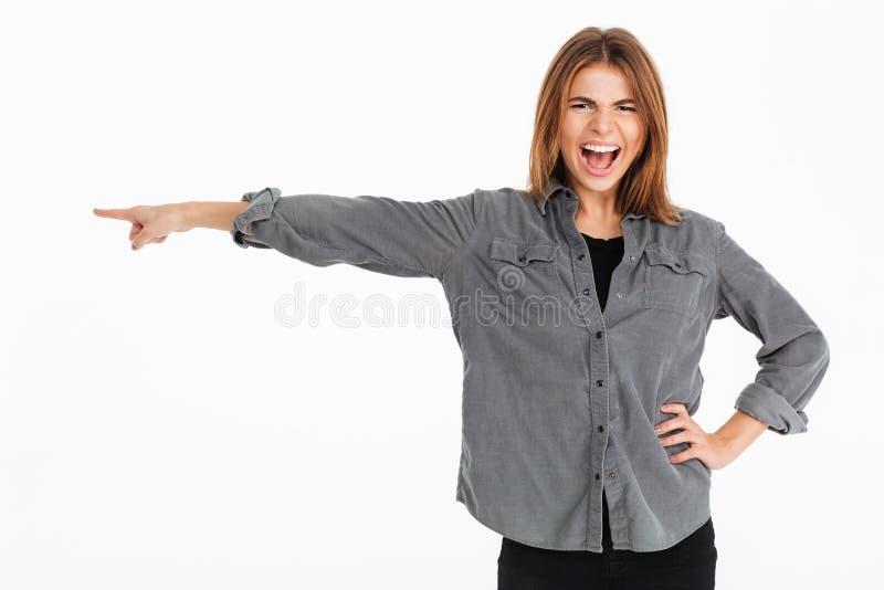 Portrait d'une jolie fille gaie dirigeant le doigt loin photo stock