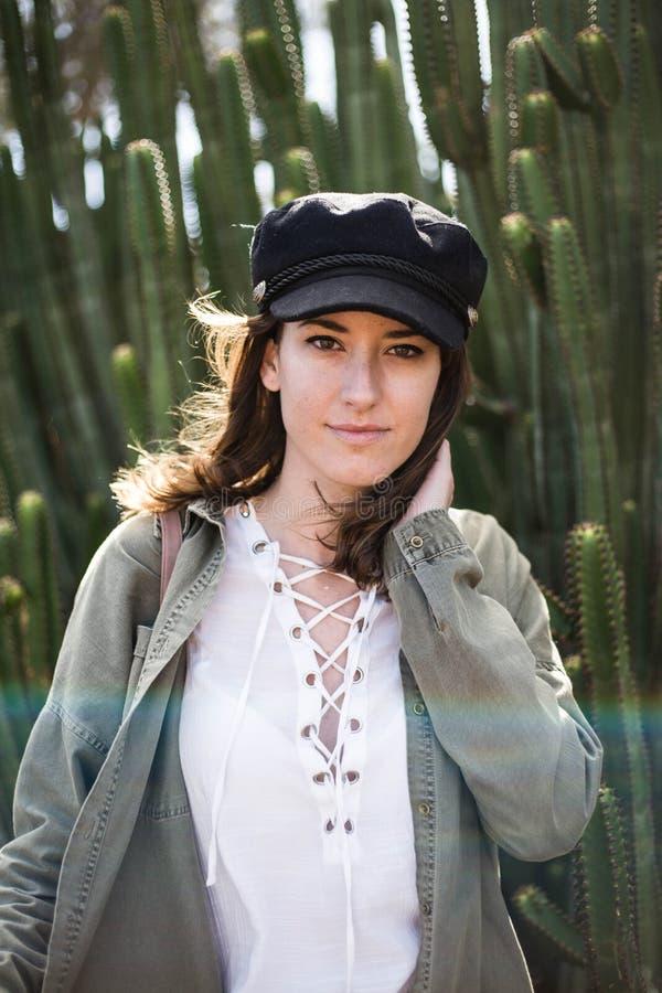 Portrait d'une jolie jeune femme avec le chapeau noir parmi le cactus photos libres de droits