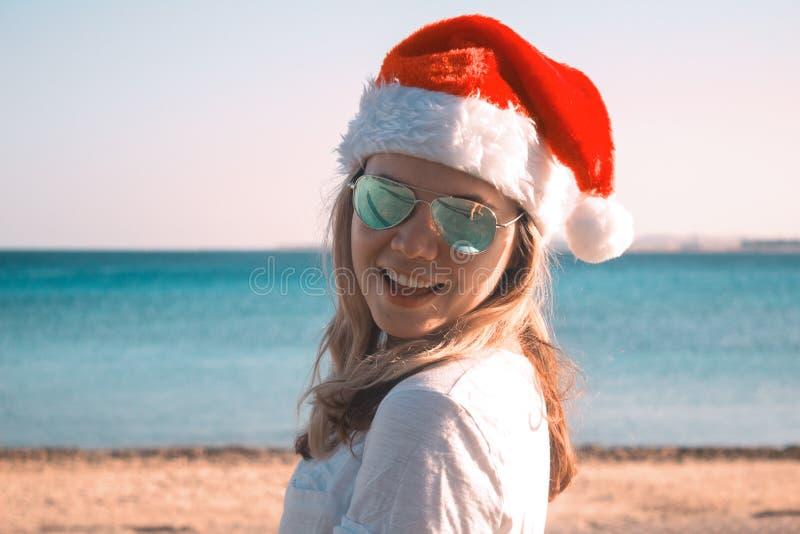 Portrait d'une jolie jeune femme dans le chapeau et des lunettes de soleil de Santa Claus sur une plage ensoleillée toned image libre de droits