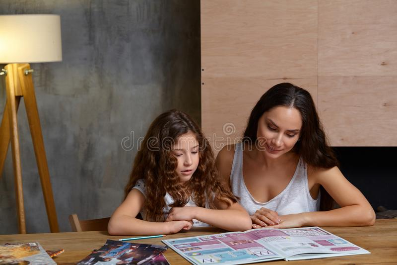 Portrait d'une m?re aidant sa petite fille douce et mignonne ? faire son travail ? l'int?rieur Famille heureux photographie stock libre de droits