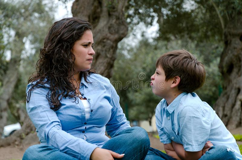 Portrait d'une mère grondant à son fils s'asseyant sur l'herbe photographie stock