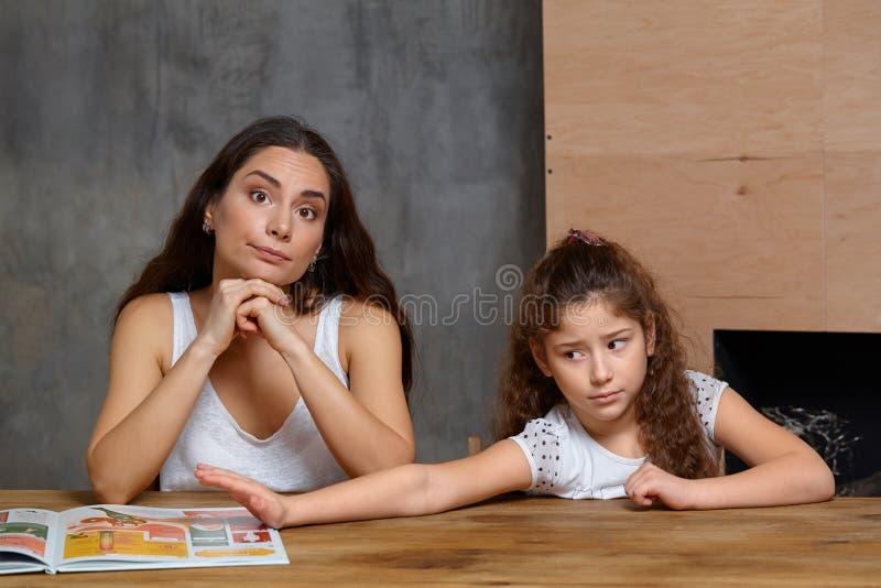 Portrait d'une m?re aidant sa petite fille douce et mignonne ? faire son travail ? l'int?rieur Famille heureux images stock