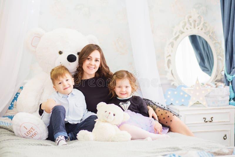 Portrait d'une m?re heureuse et de ses deux petits enfants - gar?on et fille Verticale heureuse de famille Enfants avec des jouet photographie stock