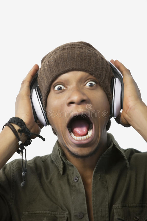 Portrait d'une musique de écoute étonnée de jeune homme d'Afro-américain par des écouteurs photographie stock libre de droits