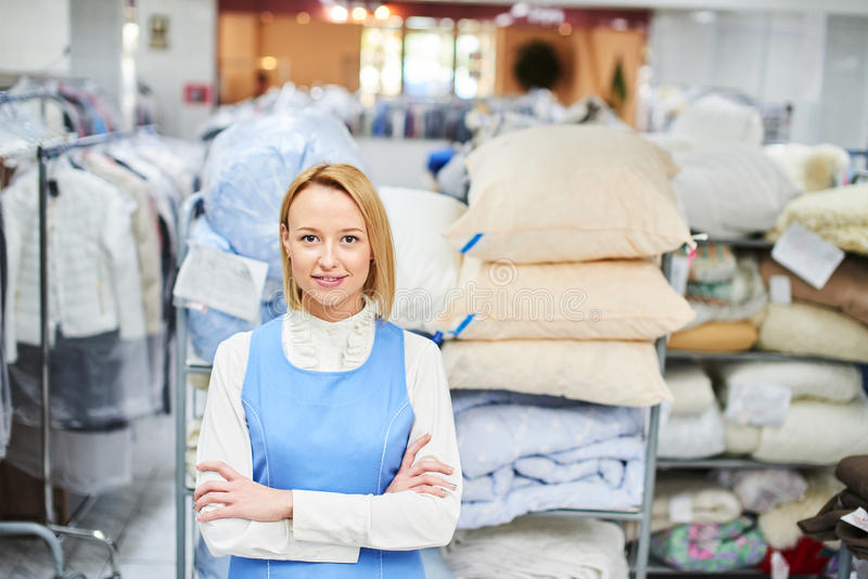Portrait d'une ouvrière de fille dans une blanchisserie d'entrepôt avec les vêtements propres images libres de droits