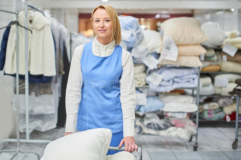 Portrait d'une ouvrière de fille dans une blanchisserie d'entrepôt avec les vêtements propres images stock