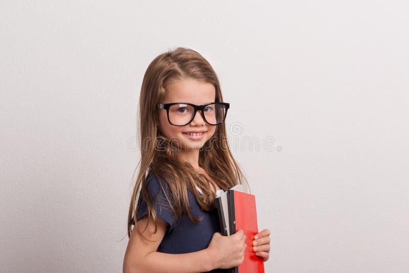 Portrait d'une petite écolière avec de grands verres dans un studio, tenant des carnets photographie stock libre de droits