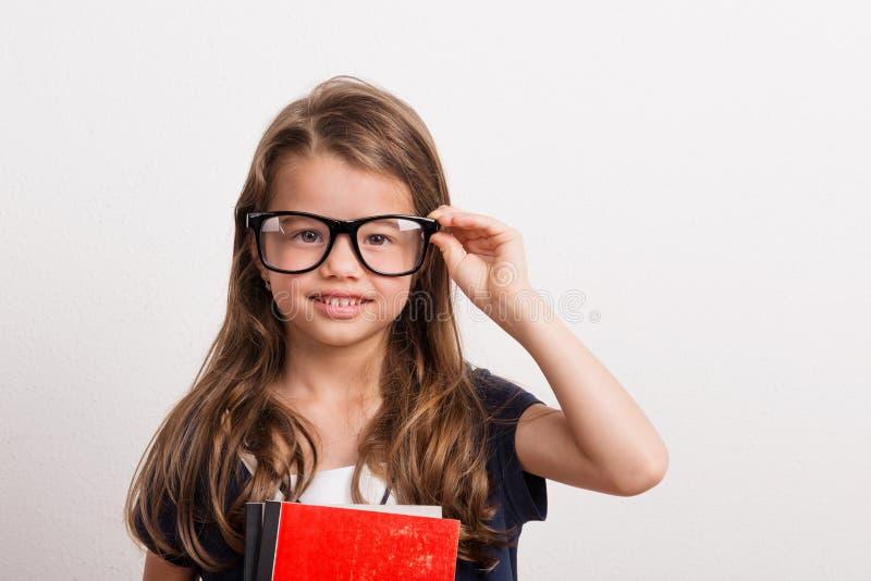 Portrait d'une petite fille avec de grandes lunettes dans le studio sur un fond blanc photo stock