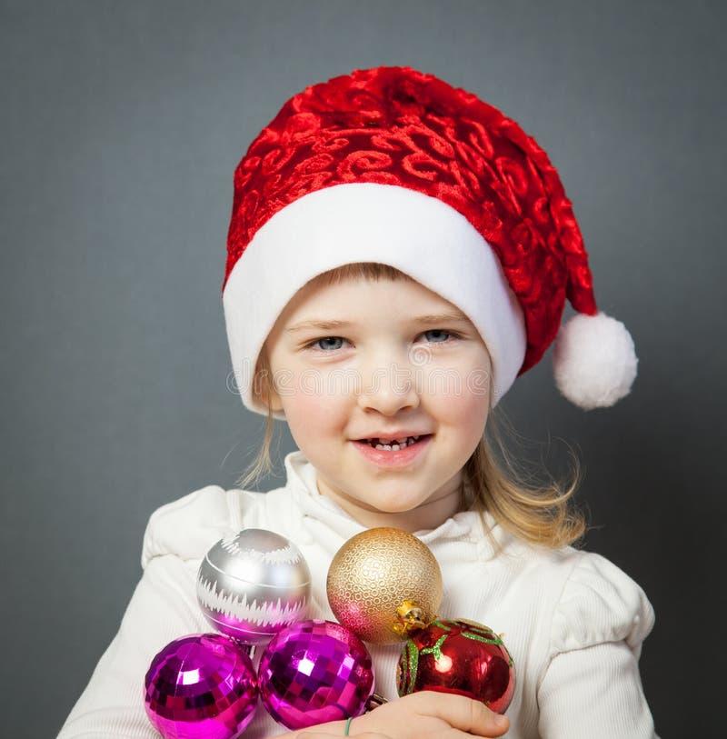 Portrait d'une petite fille avec du charme dans le chapeau de Santa image libre de droits