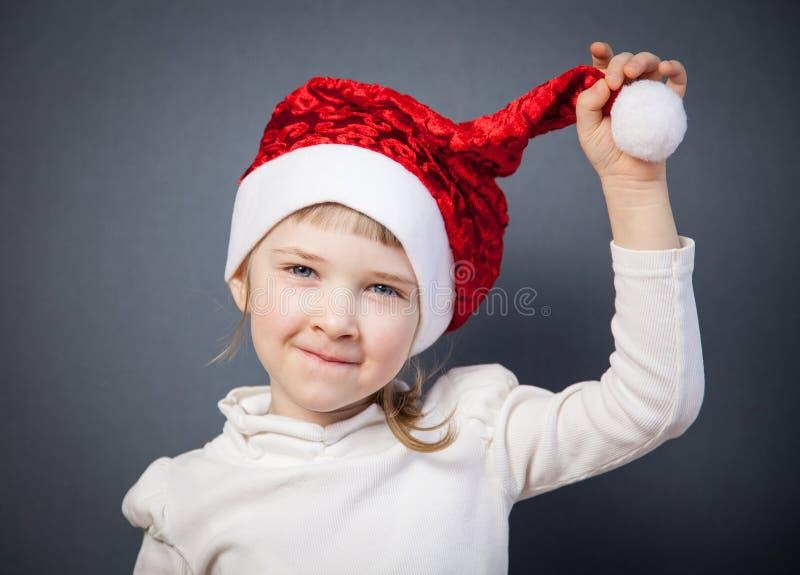 Portrait d'une petite fille avec du charme dans le chapeau de Santa photo stock