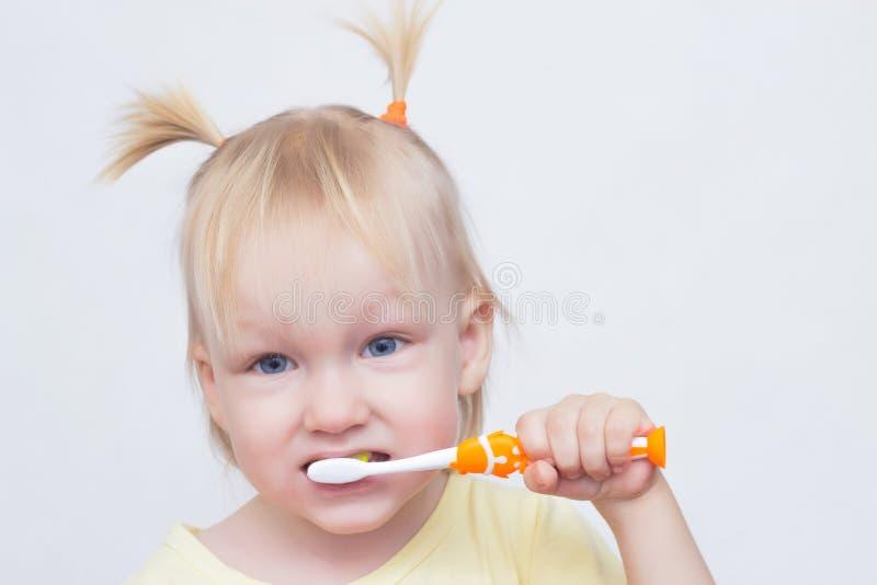 Portrait d'une petite fille blonde aux yeux bleus avec des tresses sur sa tête qui se brosse les dents avec une brosse à dents, p image stock