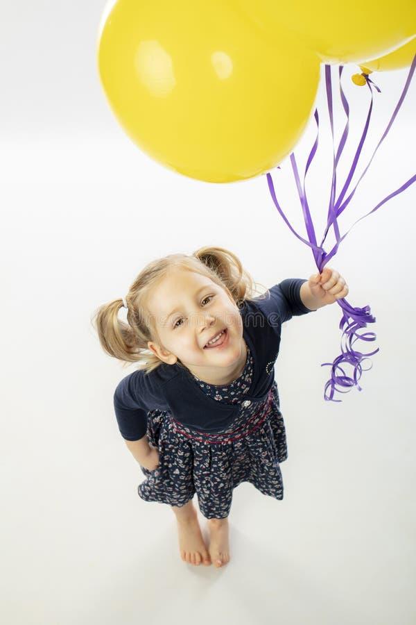 Portrait d'une petite fille blonde souriante tenant des ballons jaunes photo stock