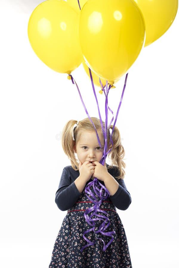 Portrait d'une petite fille blonde tenant des ballons jaunes images libres de droits