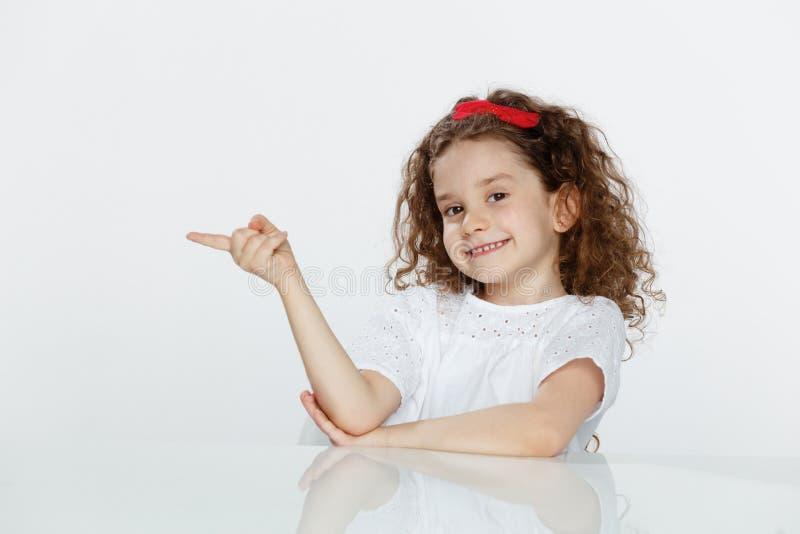 Portrait d'une petite fille bouclée adorable, posé à la table, montrant avec le doigt sur la direction, au-dessus du fond blanc photo libre de droits