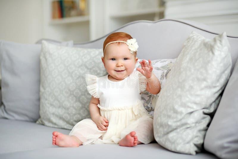 Portrait d'une petite fille de sourire mignonne dans une robe blanche dans un intérieur léger à la maison photographie stock