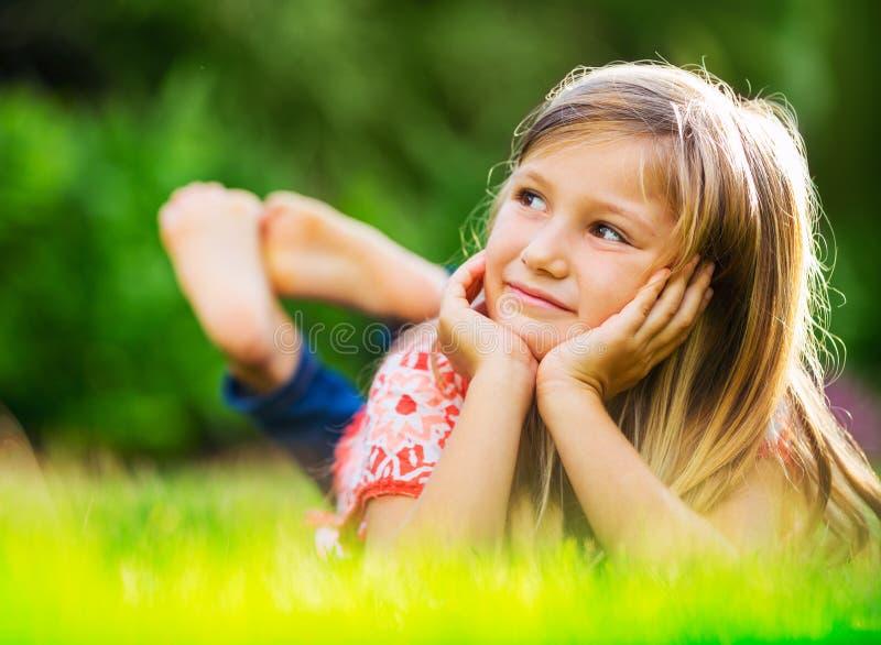 Portrait d'une petite fille de sourire se trouvant sur l'herbe verte photographie stock