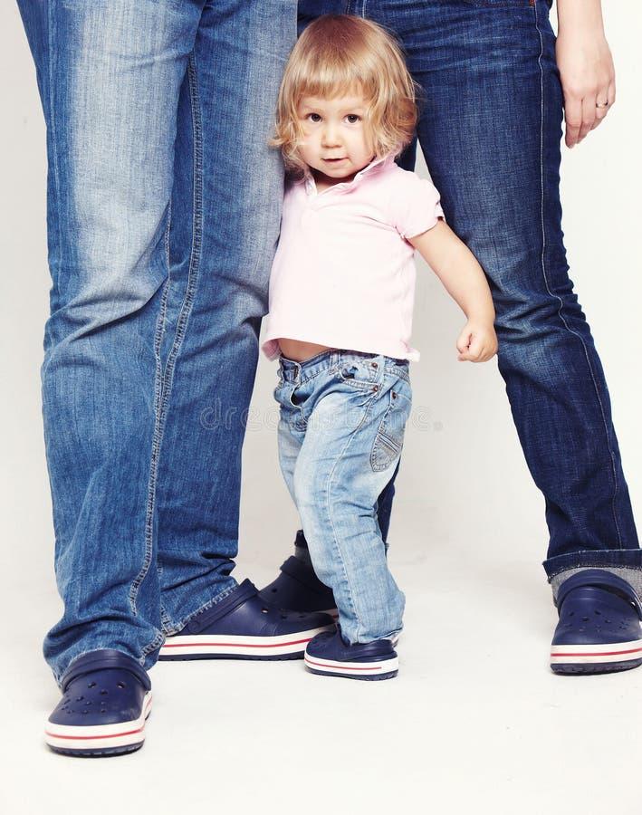 Portrait d'une petite fille mignonne dans la chemise et des jeans se tenant avec ses parents sur le fond blanc image libre de droits