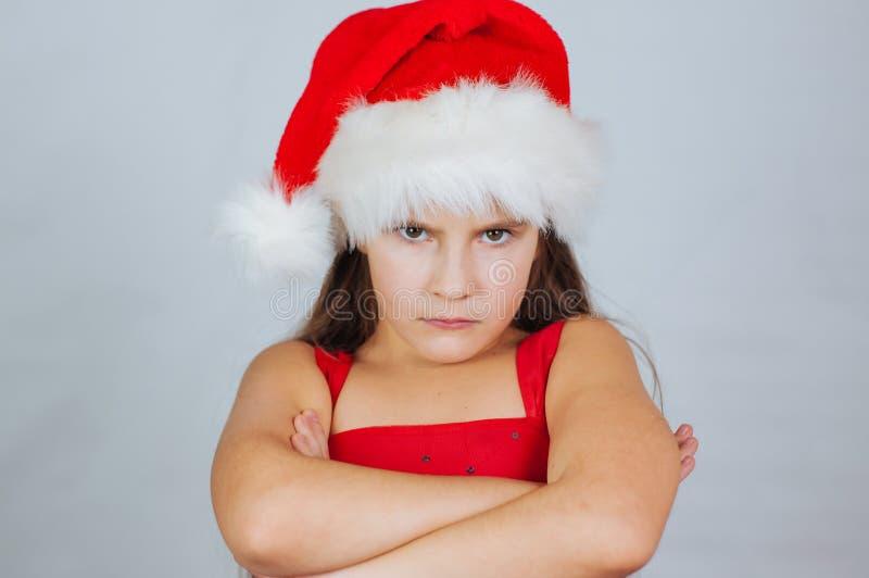 portrait d'une petite fille mignonne dans un chapeau de Noël très malheureux et en colère images libres de droits