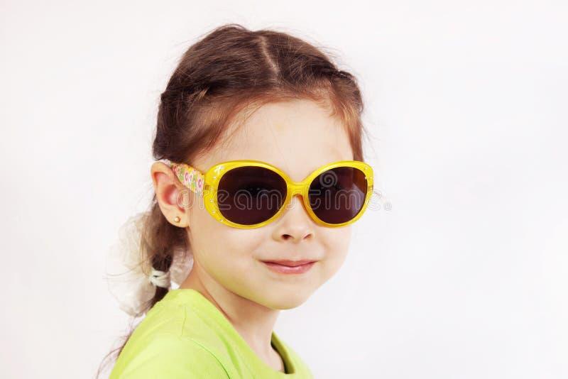 Portrait d'une petite fille mignonne de sourire avec des lunettes de soleil image libre de droits